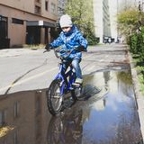 Boy child riding his bike across puddle in the street. In Hungary royalty free stock image