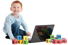 Boy child at school with computer and kids blocks. Boy learning reading with notebook computer and kids blocks. Isolated on white Stock Photos