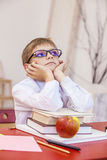 Boy, child, at school, at a school Desk with books in the glasse Royalty Free Stock Photos