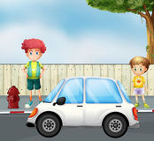 A boy and a child at the street with a car Royalty Free Stock Photos