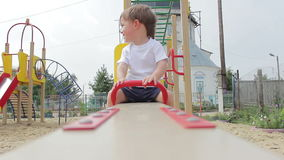 Boy child swinging up and down on a playground swing. In the summer stock video footage