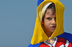 The boy, a child in a towel and hood on the beach. Royalty Free Stock Photo