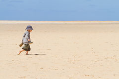 Boy child walking barefoot on sand. Boy walking barefoot on sand with sun hat Royalty Free Stock Photography