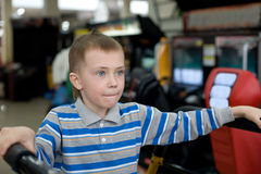 Boy in the children's amusement arcade. Playing a video game Stock Photos