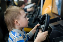 Boy in the children's amusement arcade. Playing a video game Stock Photography
