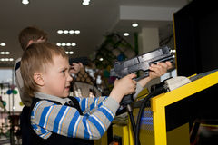 Boy in the children's amusement arcade. Playing a video game Stock Image