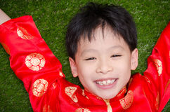Boy in chinese costume lying on grass field Stock Photography