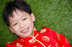 Boy in chinese costume lying on grass field Royalty Free Stock Photos