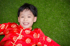 Boy in chinese costume lying on grass field Royalty Free Stock Image