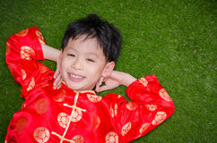 Boy in chinese costume lying on grass field Stock Photos