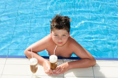 Boy with chocolate cocktail by pool Royalty Free Stock Images