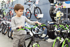 Boy chooses bicycle in sport shop Stock Photography
