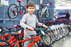 Boy chooses bicycle in sport store Royalty Free Stock Photos