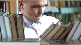 Boy chooses a book in the library. close up stock footage
