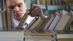 Boy chooses a book in the library. close up stock video footage