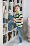 Boy chooses a book to read Royalty Free Stock Images