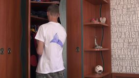 The boy chooses clothes in the closet. The boy in white t-shirt comes to closet and chooses clothes in it. Young man is preparing for his daytime. Morning time