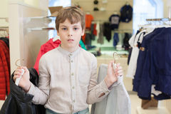 The boy chooses clothes in clothing store. The boy chooses clothes in the modern childrens clothing store stock photos