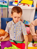 Boy chooses a colored paper. Stock Photos
