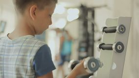 The boy chooses dumbbells for his training in the gym. The concept of sporting motivation to increase. Teenager cares about his body, figure, appearance and stock video footage