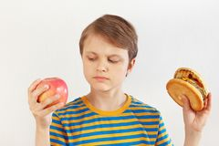 Boy chooses between hamburger and healthy diet on white background stock photography