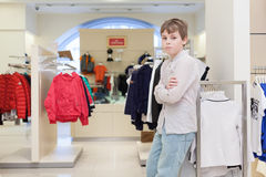 The boy chooses modern clothes in clothing store. The boy chooses modern clothes in the childrens clothing store royalty free stock photography