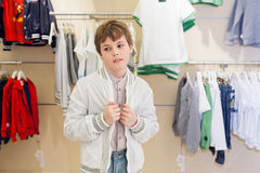 The boy chooses modern clothes in store. The boy chooses modern clothes in the childrens clothing store royalty free stock image
