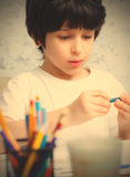 Boy chooses a pencil. For drawing. instagram image retro style Royalty Free Stock Photos