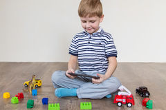 Boy chooses tablet. Boy sitting on the floor and holding a tablet royalty free stock image