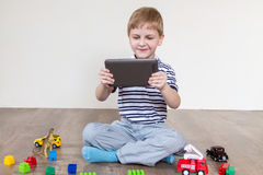 Boy chooses tablet. Boy sitting on the floor and holding a tablet royalty free stock photography