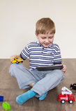 Boy chooses tablet. Boy sitting on the floor and holding a tablet royalty free stock photos