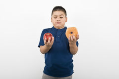 Boy Choosing Between Apple And Doughnut. Young boy choosing between an apple and doughnut isolated over white background Royalty Free Stock Photography