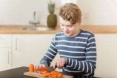Boy chopping carrots on cutting board in kitchen royalty free stock photography