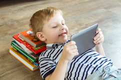 Boy chose tablet. Boy lying on the floor and plays in the tablet stock photo