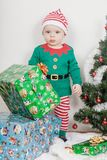 Boy in Christmas Elf costume. A baby near a Christmas tree. royalty free stock photo