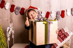 Happy boy with christmas gift near Christmas tree royalty free stock photos