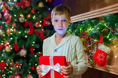 Boy with Christmas gift Opening Christmas Present In Front Of Tr. Ee Stock Image