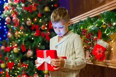 Boy with Christmas gift Opening Christmas Present In Front Of Tr. Ee Stock Images