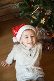 Boy in a Christmas hat in front of decorated tree Stock Image