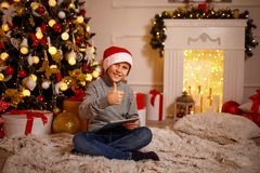Boy in Christmas hat gesturing thumb up. Happy-looking boy in Christmas hat sitting near Christmas tree, holding tablet and gesturing thumb up Stock Photos
