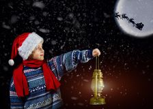 Boy in Christmas hat with lantern in hand, points the way Santa Claus flying on his sleigh with the moon. Merry Christmas Royalty Free Stock Photo