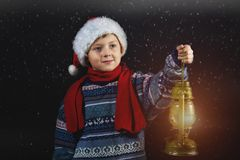 Boy in Christmas hat with a lantern in his hand. Merry Christmas Royalty Free Stock Photo
