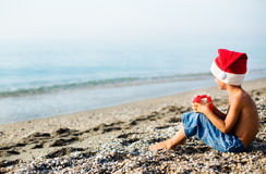 Boy in Christmas hat next to the sea Stock Images