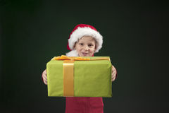 Boy with christmas hat and present on dark green Stock Images