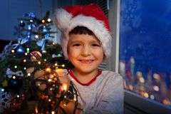 Boy with Christmas lights garland smiling stock image