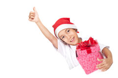 Boy in christmas red hat showing thumbs up Stock Images