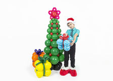 A boy with Christmas tree and balloons gifts Stock Image