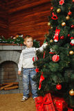 Boy, Christmas tree and gifts. Boy shot on background with Christmas tree, gifts and fireplace Stock Images