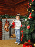 Boy, Christmas tree and gifts. Boy shot on background with Christmas tree, gifts and fireplace Royalty Free Stock Photos