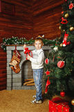 Boy, Christmas tree and gifts. Boy shot on background with Christmas tree, gifts and fireplace Royalty Free Stock Photography